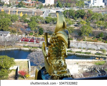Top view from Osaka castle, golden fish with a dragon like-head is called a Shachihoko were placed on the roof, canal, garden and red tram that tourists can take for sightseeing around castle