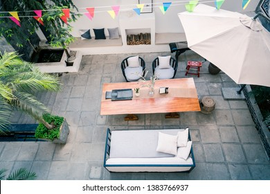 Top view outdoor terrace garden table with pillows with plants, sofa and umbrella.