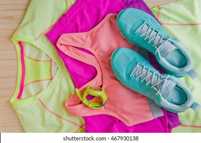 Top view of outfit for runner on wooden background: running shoes, shorts, shirt, and sport bra. Horizontal orientation.