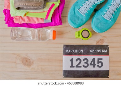 Top view of outfit for runner on wooden background: bib number, bottle of water, gps watch, running shoes, running waist bag, shorts, shirt, and sport bra. Horizontal orientation.