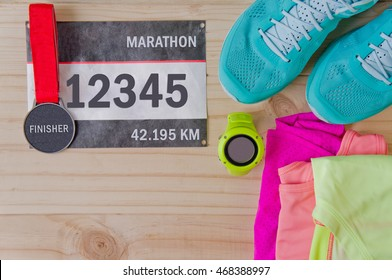Top view of outfit for runner on wooden background: bib number, finisher medal, gps watch, running shoes, shorts, shirt, and sport bra. Horizontal orientation.