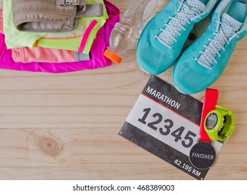 Top view of outfit for runner on wooden background: bib number, finisher medal, bottle of water, gps watch, running shoes, running waist bag, shorts, shirt, and sport bra. Horizontal orientation.