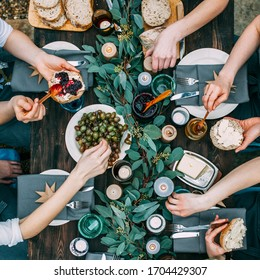 Top view over a dining table, decorated with eucalyptus leaves, with tableware and food. Backyard picnic with friends or neighbors.