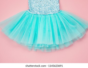 Top view over the girl ballet tutu dress over the pink background. Delicate details of the dress for little princesses