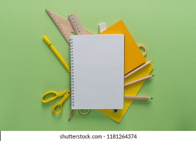 Top view over a notebooks, pencils, scissors, rulers, tapes and eraser on a green background. Back to school concept. Office supplies flat lay.