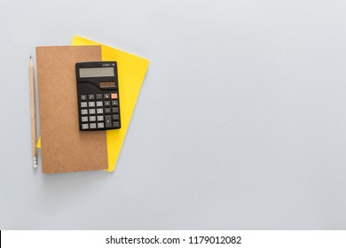 Top view over the working desk with notebook, pencil and calculator. Copy space for text. Flat lay of a workplace on white background.