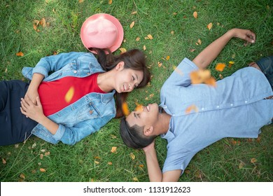 Top view over young Asian couple lying on green grass in the outdoor park or garden in summer time.