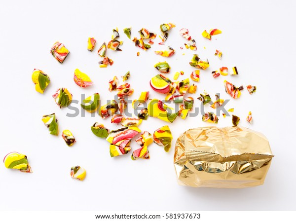 top view of packaged various chocolate pralines and roughly broken lollipops on white background. Sweet sucker, lollipop, candy, minimal concept above decoration, food background