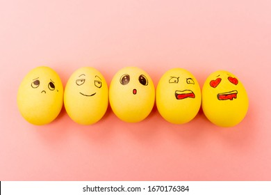 Top view of painted Easter eggs with different facial expressions on pink background