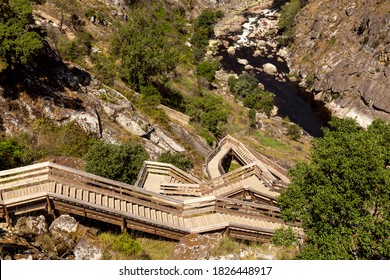 Top view of the Paiva's walkways. Wooden walkways at Paiva river. In the foreground we see the curves of the walkway and in the background, between the mountains, we see the river and the rocks.
