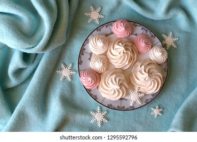 Top view of pale pink and white meringue on a plate decorated with snowflakes on a table covered with a cloth. Delicious Winter sweets. Confectionery Art. Winter mood concept.