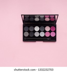 top view Palette of multicolor cosmetic make up with a mirror on pink background, pink and grey eye shadow palette, colorful shadows minimalism, on light pink background