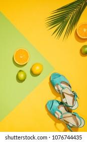 top view of palm leaf, stylish female blue platform sandals, lemons, limes and slices of orange