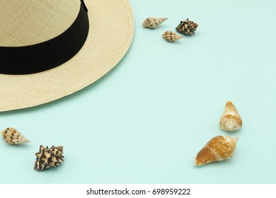 Top view  Panama-style caps (panama hat) lay on a blue sky color background, with shells placed around the summer concept. copy space.