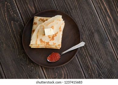 Top view of pancakes in pile with spoon of red caviar