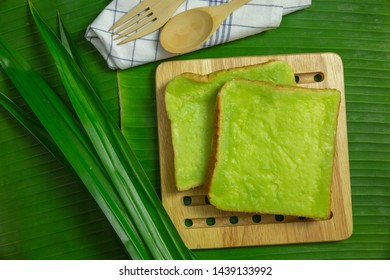 Top view pandan custard topping sliced bread and pandan leaf on banana leaf background