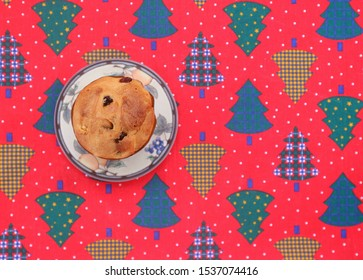Top view of Panettone, the traditional italian sweet bread loaf, on a red tablecloth decorated with motifs in shape of Christmas trees. Background for copy space.