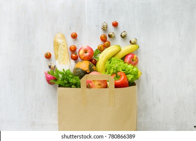 Top view paper bag of different fresh health food on white wooden background. Top view. Flat lay