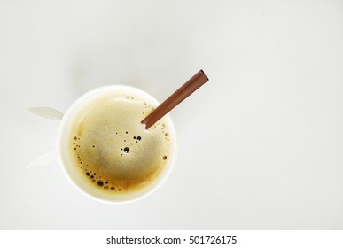 Top view of a paper cup of black coffee on white table