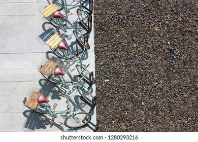 ฺBicycle top view parking in a row contrast with a stones background and cement ground