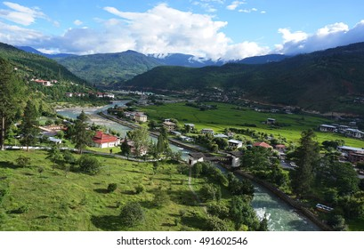 A top view of Paro village, river, mountains, and bridge with cloudy blue sky, Bhutan during summer.