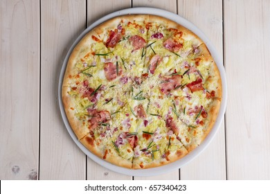Top view of part of pizza with bacon chips, ham, cheese and rosemary.