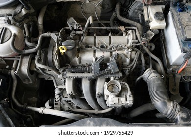 Top view of a partially disassembled engine of a modern car during repairs. Removed intake manifold, ignition coils. The engine is dirty.