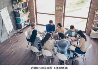 Top view of partners  in casual clothes. They are focused, discussing the ideas for new start-up at nice comfortable  office - Shutterstock ID 645808588