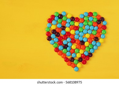 Top view party table with heart shape candies.