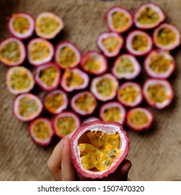 Top view passion fruits cut in half in heart shape background, kind of seedy fruit or passiflora edulis with soft pulp and seeds inside hard rind