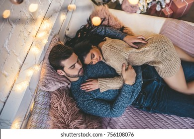Top view of passionate romantic couple spending time before New Year at home with garlands. Sexy young woman and handsome man are lying on bed in sweaters and hugging. Tender couple sleep together