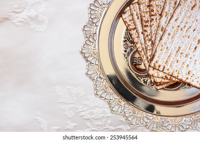 top view of passover background. matzoh (jewish holiday bread) and traditional seder plate over white tablecloth