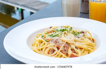 Top view Pasta alla carbonara at restuarant table. Carbonara pasta, spaghetti with pancetta, egg, hard parmesan cheese and cream sauce. Traditional italian cuisine.