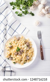 Top view pasta with mushroom and parsley on white wooden table.