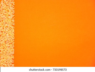 Top view of pasta. Raw spilled Italian pasta view from above on orange background alphabet.