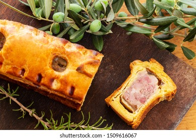 Top view of a pate en croute or pâté en croûte or meat pie, with rosemary twig and green olives on branch with leaves over a dark wooden cutting board and a used oak wood background. French traditiona