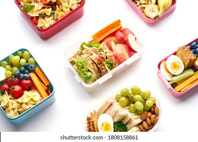 Top view pattern with school lunchboxes with various healthy nutritious meals on white background. Lunch food from above