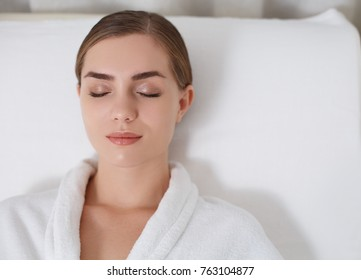 Top view of peaceful girl sleeping on massage bed at wellness center. Her eyes are closed with enjoyment. Portrait