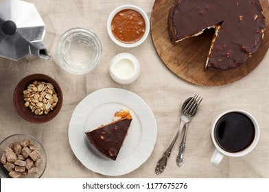 Top view of Peanut Butter Chocolate Caramel Cheesecake Pie and cup of coffee on dining table with linen tablecloth. A Sweet Coffee Break concept