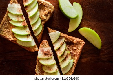 Top view of peanut butter toasts topped with thinly sliced green apples and ground cinnamon.