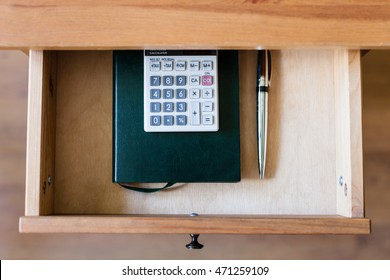top view of pen, calculator and notebook in open drawer of nightstand