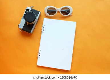 top view pen notbook, camera, glasses, on an orange background with space for text. flat lay