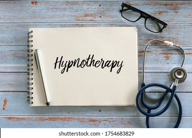 Top view of pen,glasses,stethoscope and notebook written with Hypnotherapy on wooden background.