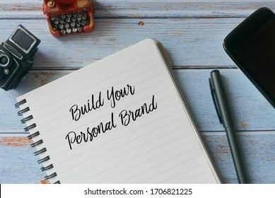 Top view of pen,mobile phone,vintage toy of camera and typewriter with notebook written with Build Your Personal Brand on wooden background.