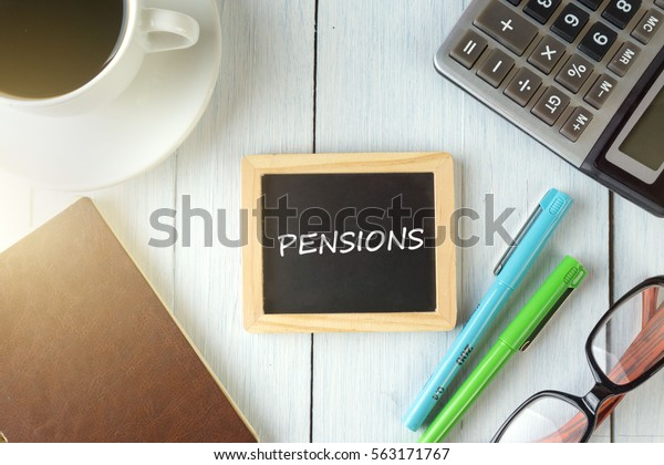 top view of PENSIONS written on the chalkboard,business concept.chalkboard,notebook,calculator,pen,glasses,coffee on the wooden desk.