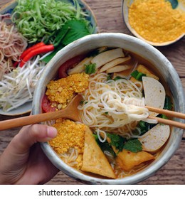 Top view people eating bowl of homemade vegan rieu noodle soup or vegetarian crab paste vermicelli soup; a traditional Vietnamese dish; plate of vegetables; herbs; ready to eat on wooden background