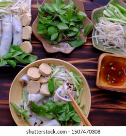 Top view people eating breakfast with Vietnamese vegetarian rolled steamed rice pancake or banh cuon with herb and sauce at home on wooden table