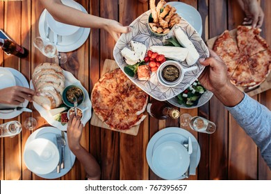 Top view of people eating meal at table served for party. Friends celebrating housewarming party on wooden table. Male hands passing food plate to female guest.