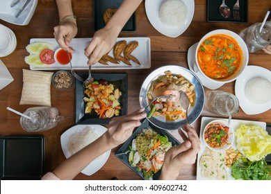 Top view of people eating Thai food on wood table together.