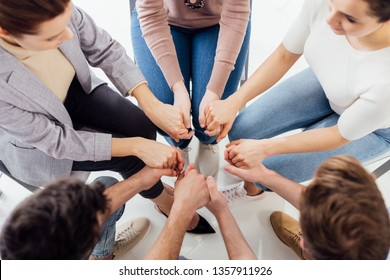 top view of people holding hands during group therapy session